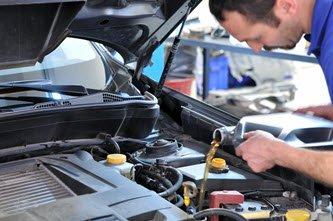 Mechanic adding oil to vehicle