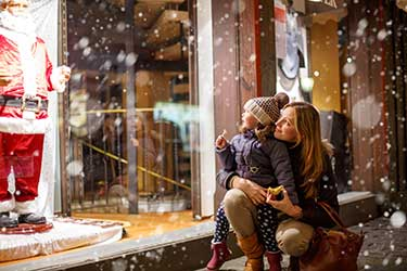 Mother and daughter looking in christmas decorated store window
