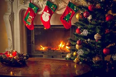 Christmas tree beside a fire with stockings hung