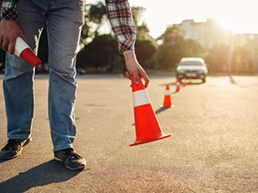 man putting pylons down for defensive driving practice