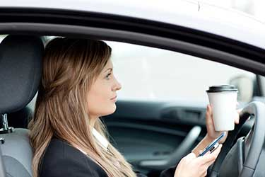 Women with a phone and coffee in her hands while driving