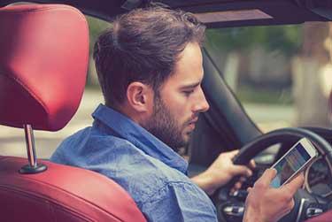 Man looking at his phone while driving