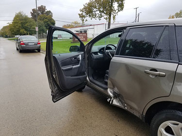 Grey SUV with damaged rear door