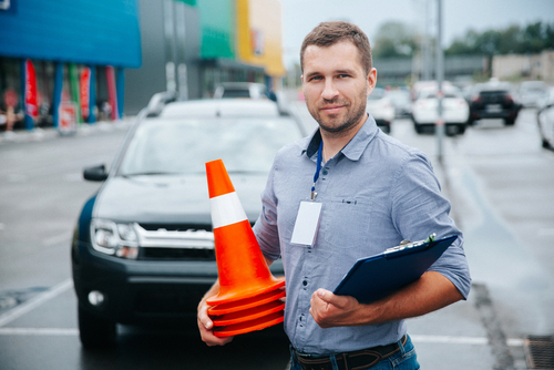 Male driving teacher holding pylons