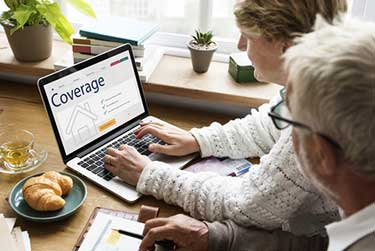 older couple looking at insurance coverage on a laptop