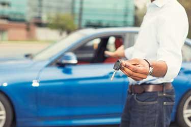 Man handing keys over to a blue car