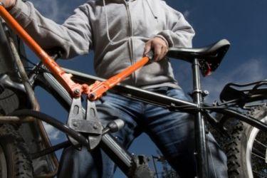 Man cutting a lock on a bike