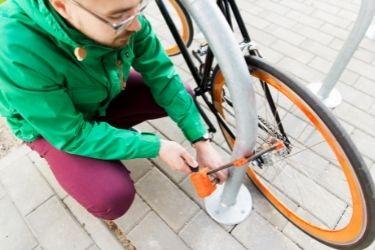 Man with green jacket locking orange bike