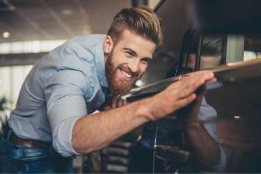 man with beard looking at car