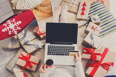 Woman shopping on laptop with presents around her