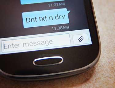 Smart phone text saying dnt txt n drv