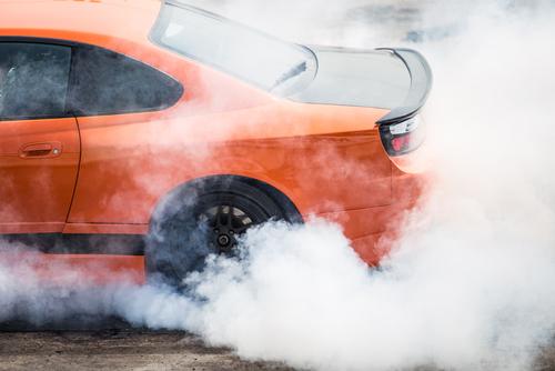 Orange car stunt driving doing a burnout