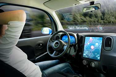 man in a self-driving car relaxing