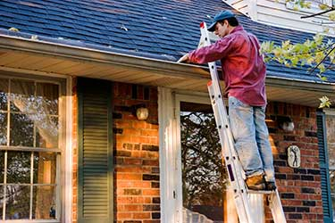 man cleaning eavestrough