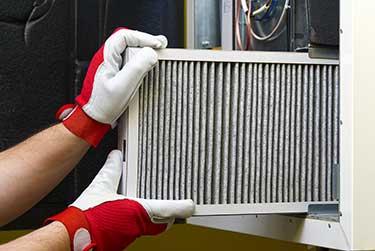man replacing filter in a furnace