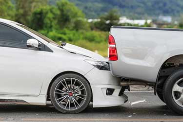 white car and white truck in an accident