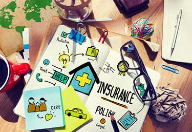 visual collage on a desk of different types of insurance