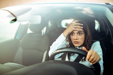 Woman in white shirt expressing frustration while driving