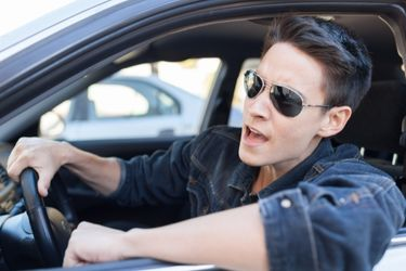 Young man with sunglasses in car stressed out